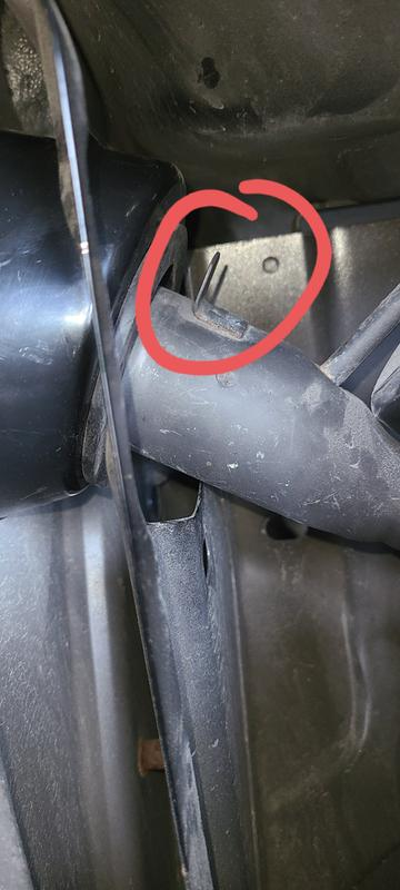 Tab on Jeep's fuel tank stem prevents Smittybilt fuel door casing from going into opening. View is from rear with driver-side tail light removed.