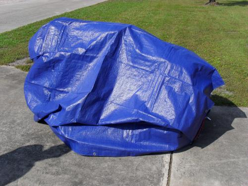 Riding mower covered with all purpose tarp