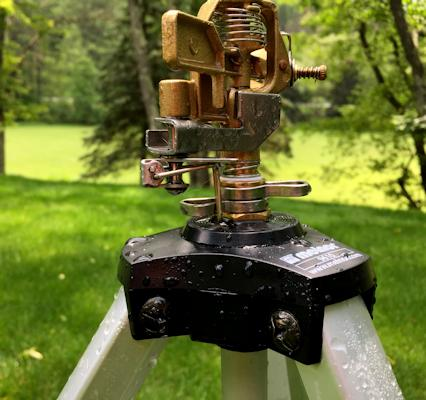 The sprinkler with the stop arm engaged and pressed up against the metal stops