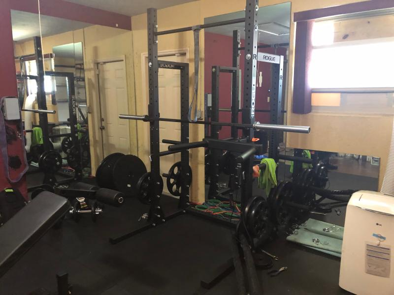 Rep fitness half rack with rogue barbell and iron rep bumpers